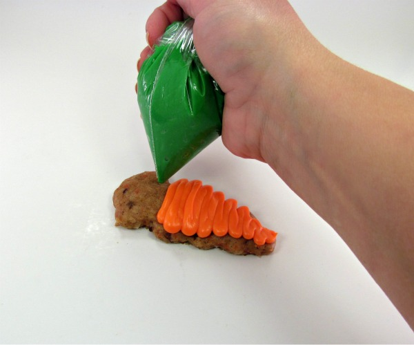 green frosting in bag being squeezed onto carrot cake cookie